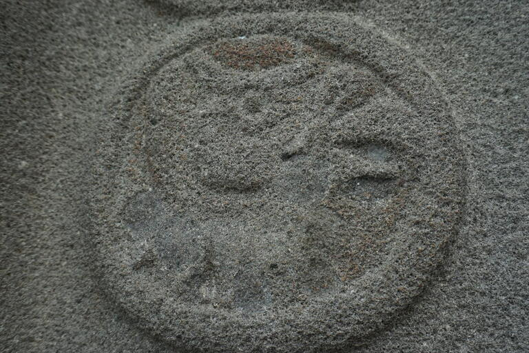 bas-relief stone carving, circle with vague bird shape inside