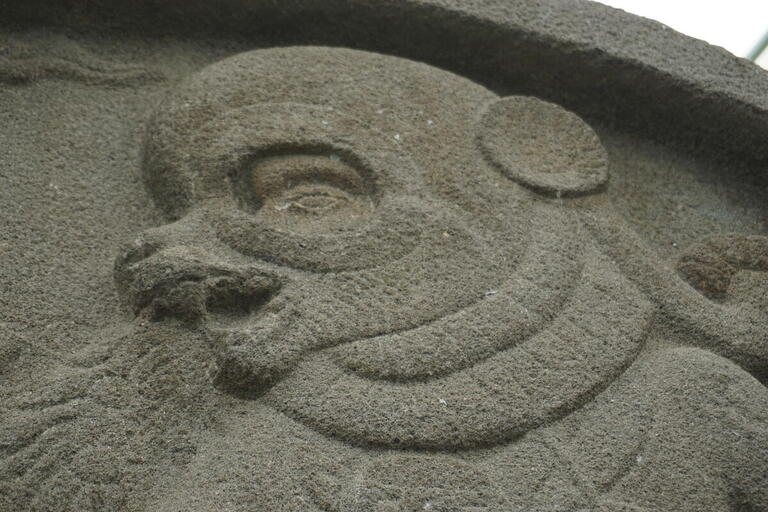 bas-relief stone carving of human figure wearing animal mask, in profile, mouth open
