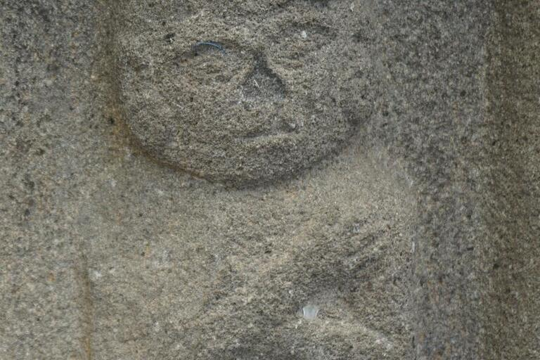 bas-relief stone carving, seated figure, arms crossed, wearing crown of some sort
