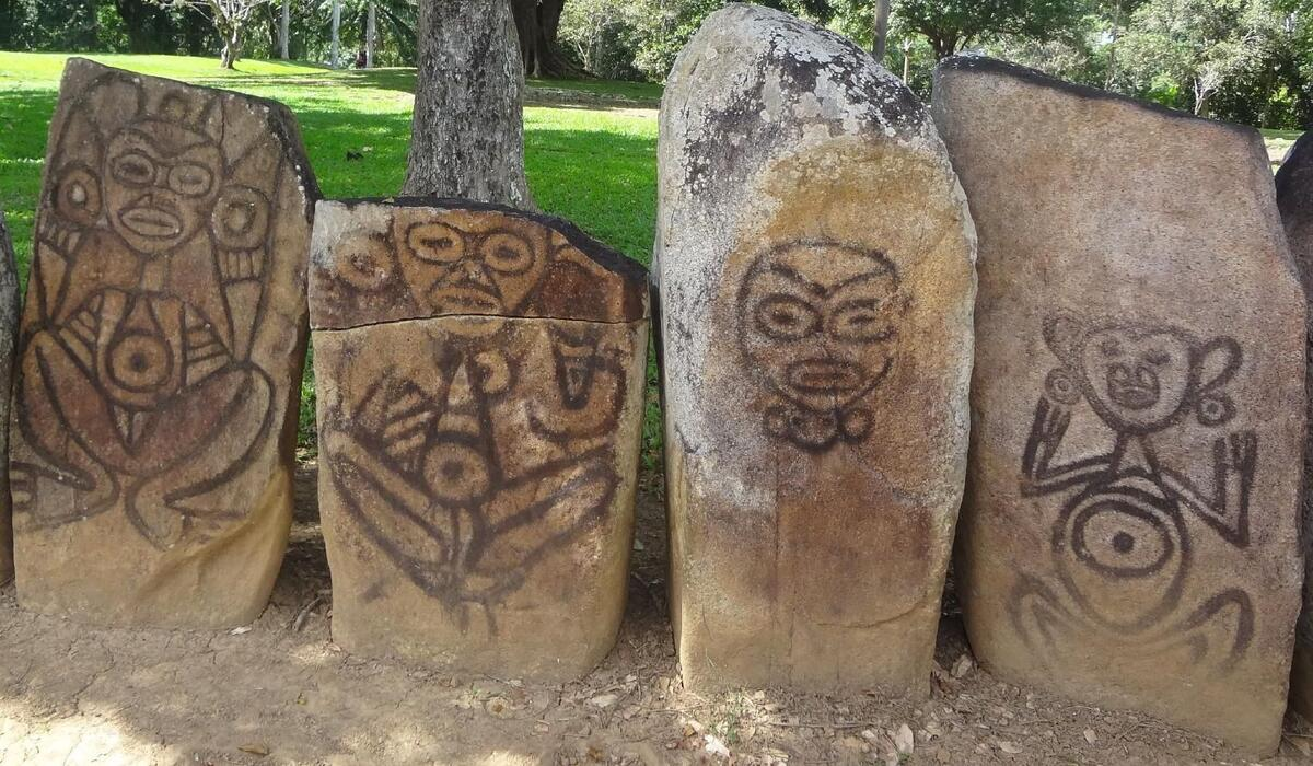 Four large stones with petroglyphs of stylized images of people.
