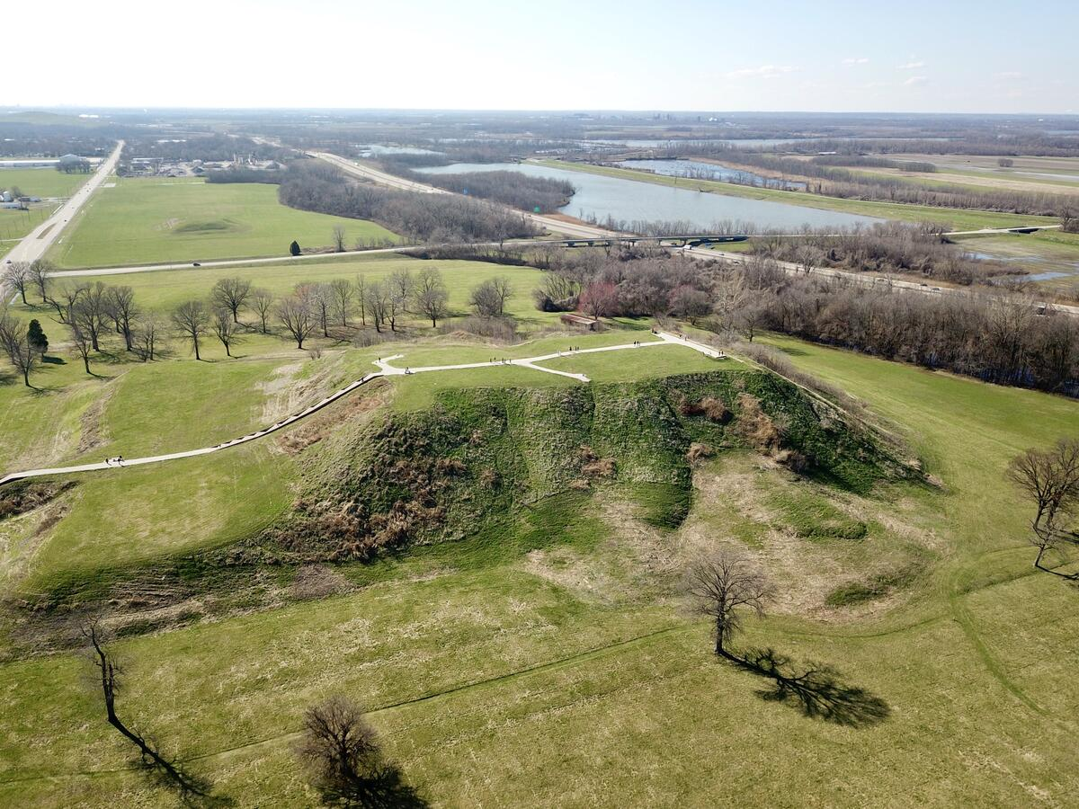 Aerial view of huge mound at Cahokia, surrounded by flat land with grass and trees, Mississippi river in distance