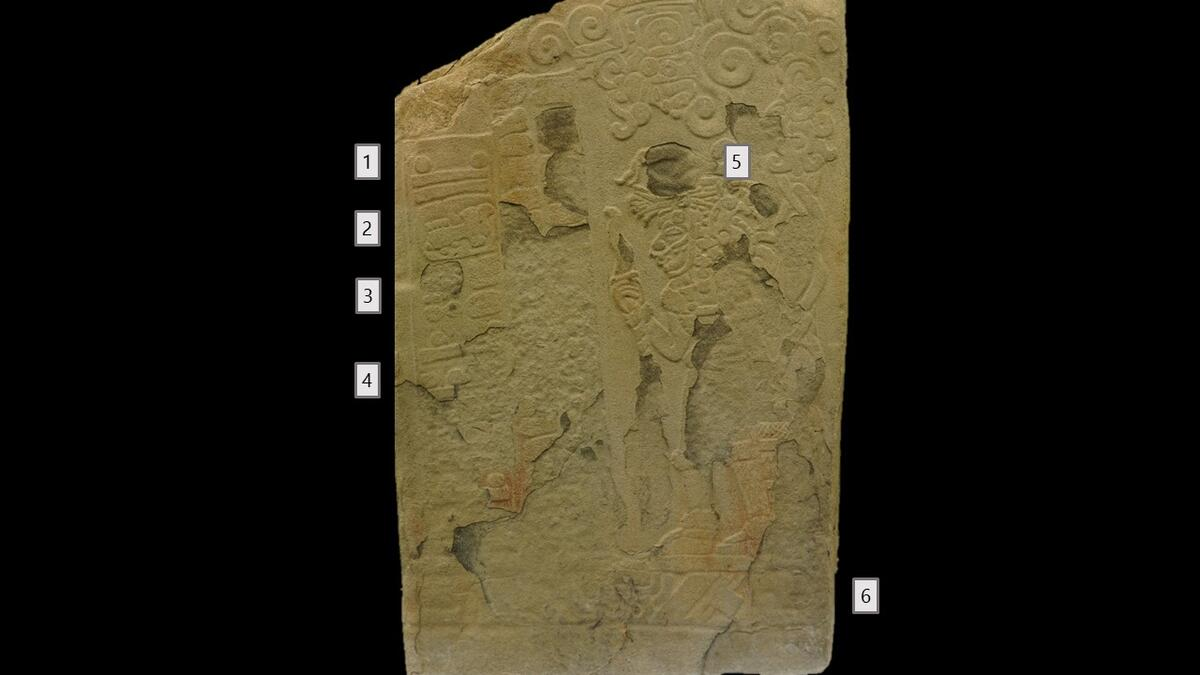 bas-relief stone carving, man in profile holding staff, symbols