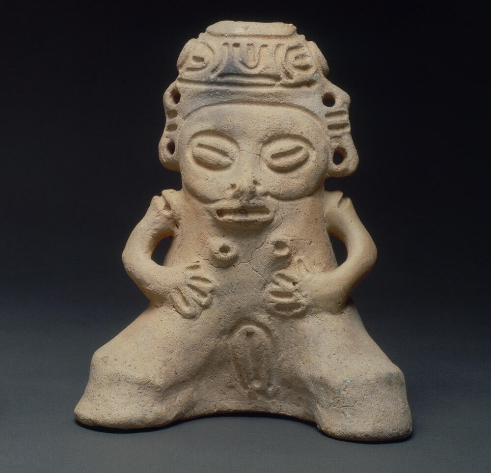 ceramic female figure with face, arms and legs, plus breasts and vulva