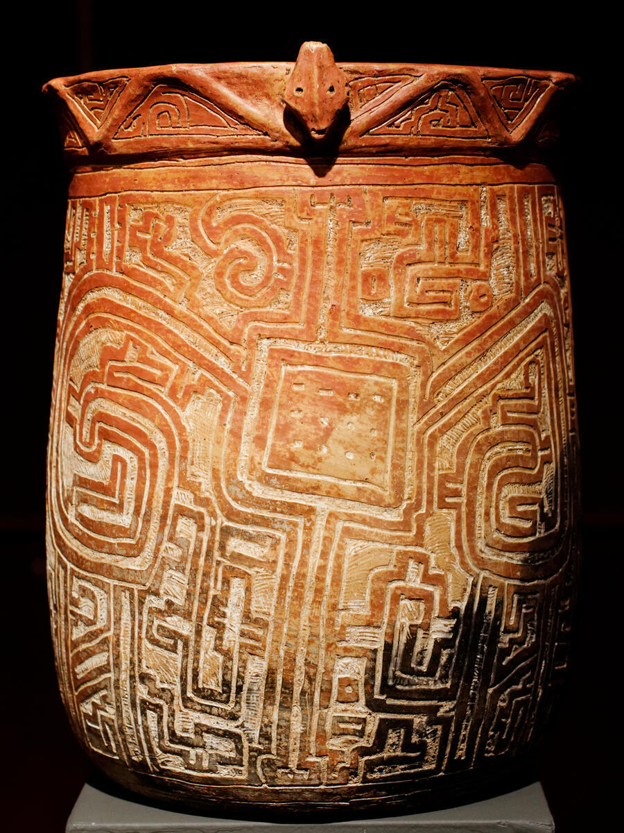 Ceramic cylinder-shaped vessel decorated with geometric carvings and face at the rim.