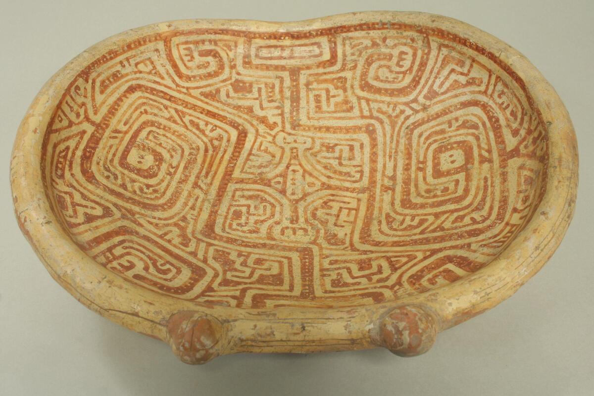 Oval dish with geometric design that looks like a series of coiled snakes.
