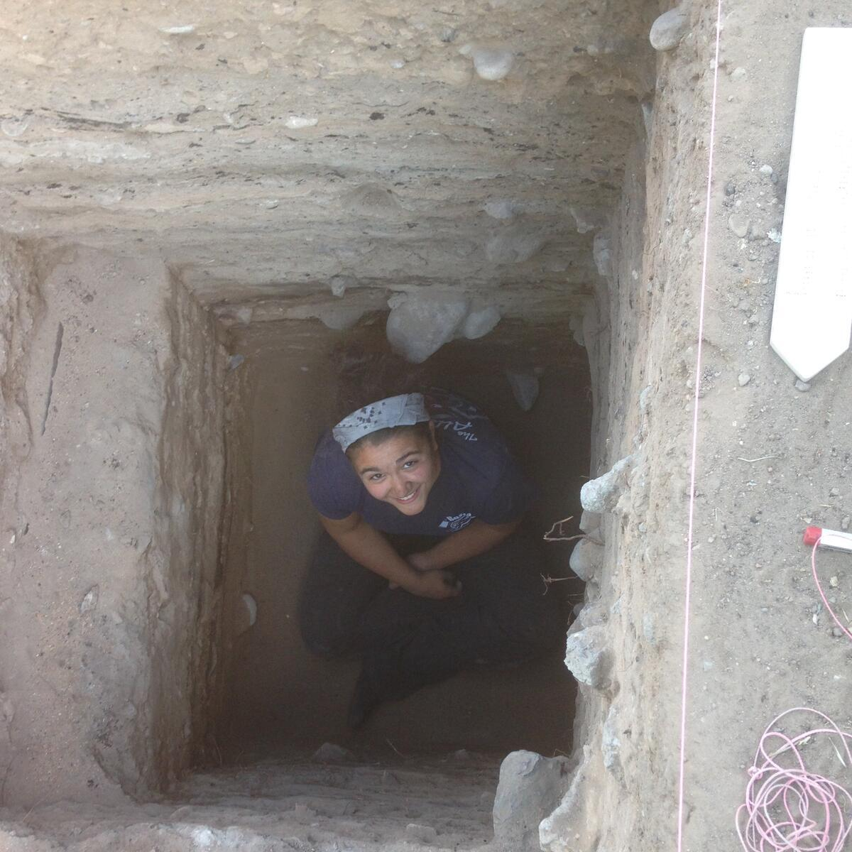 Person sitting in deep, square hole while looking up at camera, smiling.