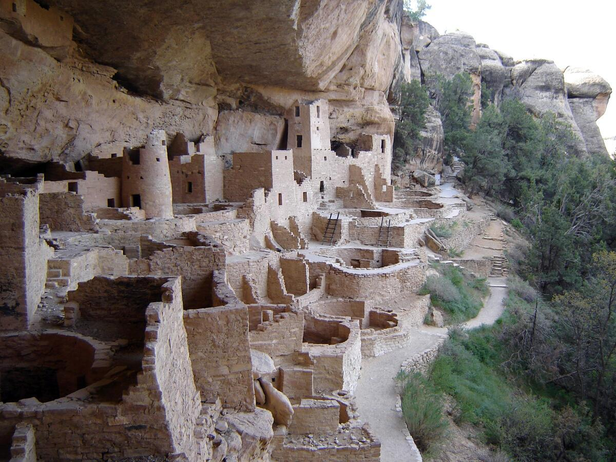Multi-story stone buildings built under a cliff overhang on the edge of a steep cliff.