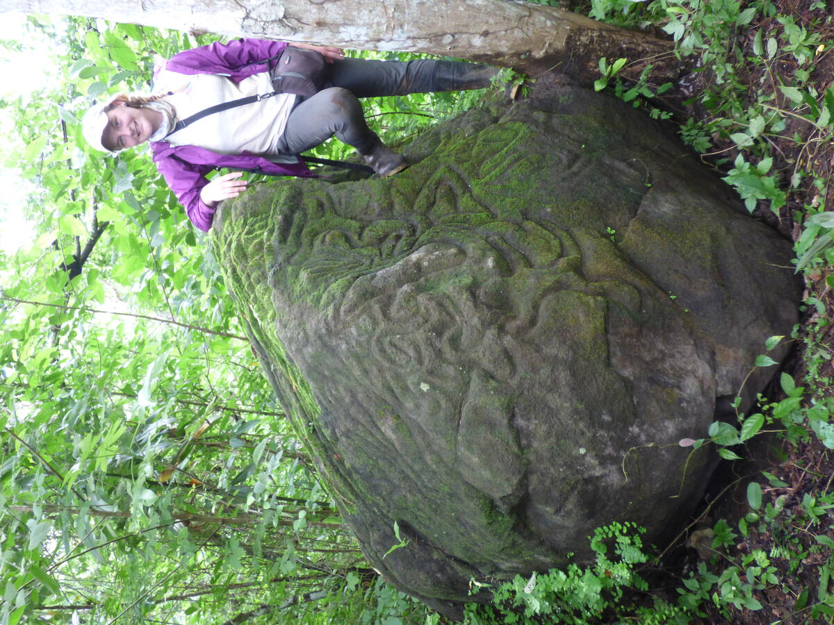 woman standing next to large boulder covered in carvings