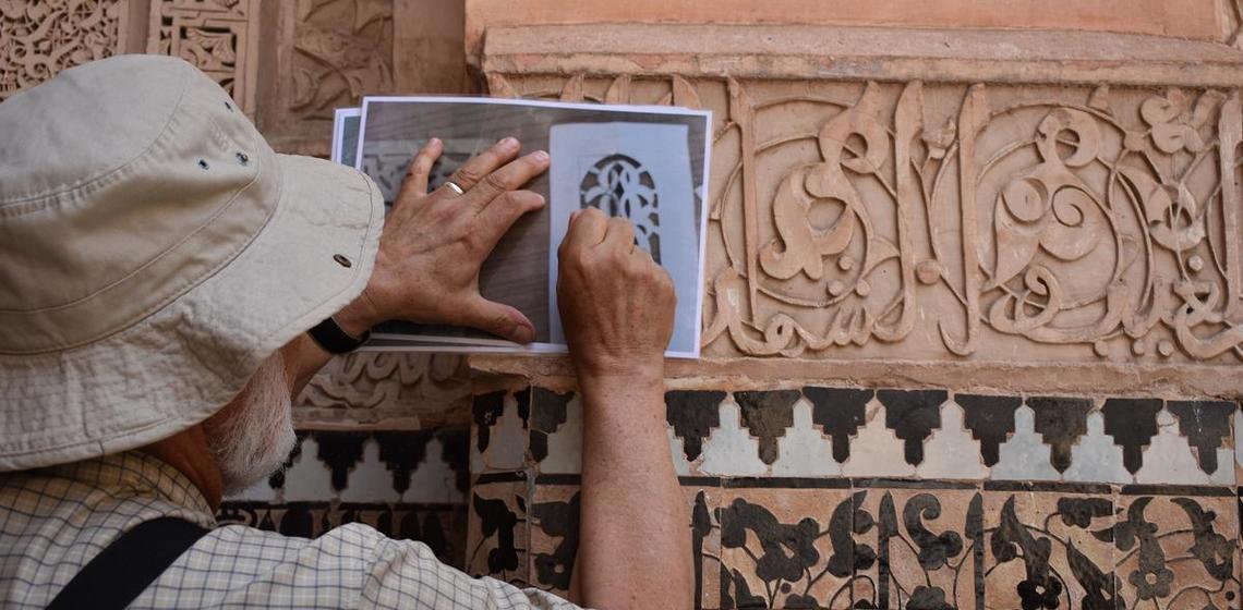 examining calligraphy at Madrasa Ben Youssef, Morocco