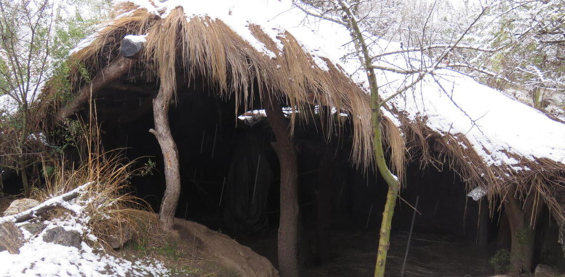 roof extending up from ground-level, snow on both roof and ground, interior visible between ground and roofline